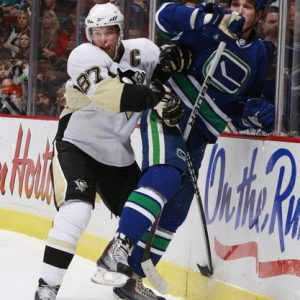 VANCOUVER, CANADA - JANUARY 16: Sidney Crosby #87 of the Pittsburgh Penguins checks Shane O'Brien #55 of the Vancouver Canucks into the boards during their game at General Motors Place on January 16, 2010 in Vancouver, British Columbia, Canada. (Photo by Jeff Vinnick/NHLI via Getty Images)