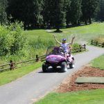 Emily having fun driving the pink camouflage golf cart.