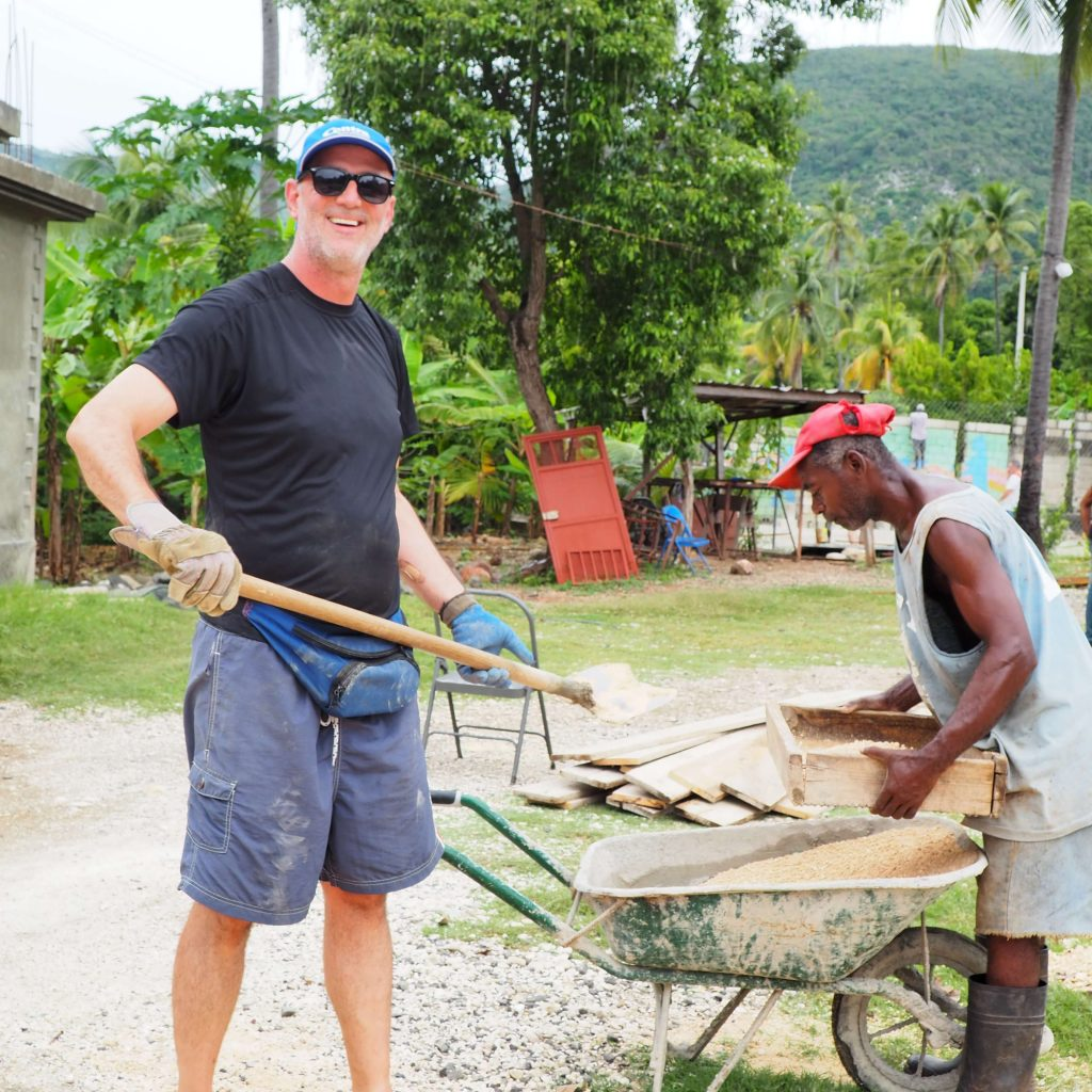 Andrew Creighton working with the locals loading a wheelbarrow.